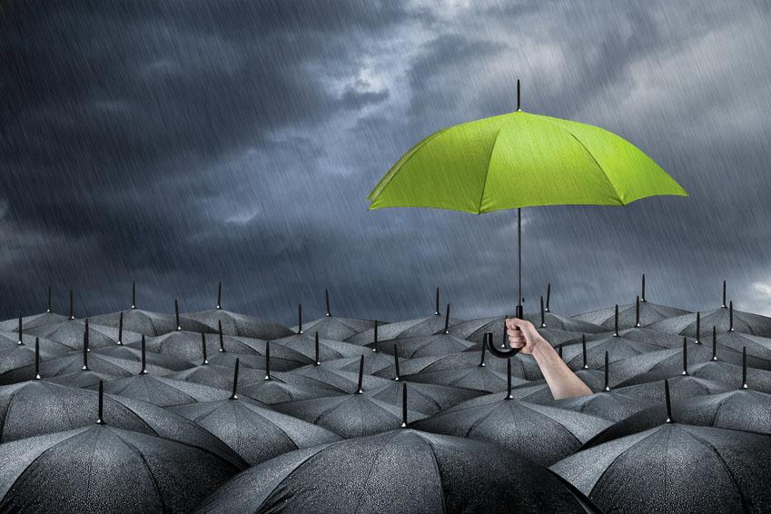 Hilfe durch grünen Schirm über schwarzen Schirmen