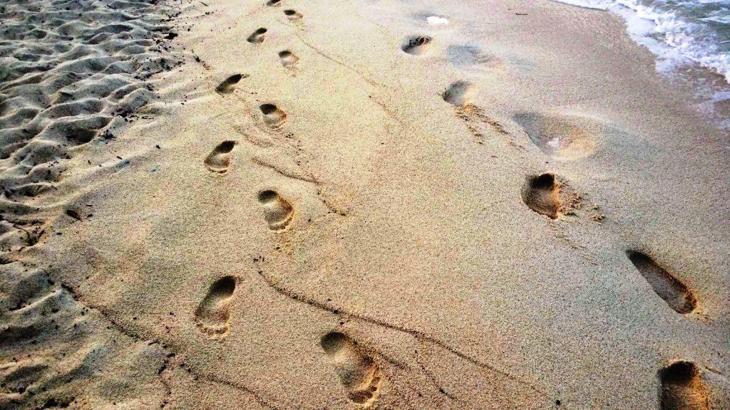 Achtsamkeitstraining zeigt Fußabdrücke im Sand